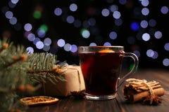 被仔细考虑的酒、礼物和香料在圣诞灯背景  在树旁边的桌上 免版税库存图片