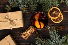 被仔细考虑的酒、礼物和香料在桌上在树旁边 圣诞节和新年,装饰的概念 图库摄影