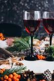 被仔细考虑的酒在玻璃、红色莓果、爆沸和秋天在木桌上分支 免版税库存照片