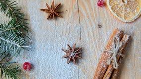 被仔细考虑的酒或圣诞节面包店桔子的,茴香,桂香,在木背景的新鲜的红色荚莲属的植物莓果搽粉的香料 库存照片