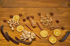 被仔细考虑的酒的成份:干果子,桔子,角豆树,姜,桂香,茴香棍子担任主角,在木棕色背景的坚果 免版税库存图片