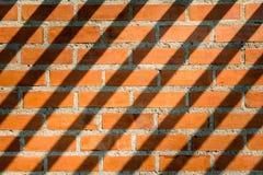 被仿造的砖墙褐色和有长的阴影 库存图片