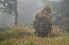 被伪装的狙击手在有雾的森林里 免版税库存图片