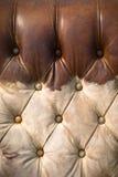 被佩带的棕色皮革老沙发垂直 免版税库存图片