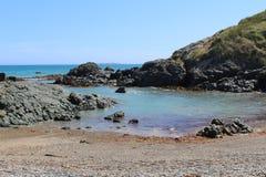 被保护的多岩石的海滩小海湾 图库摄影