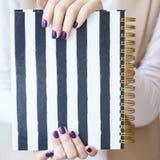被修剪的妇女` s手特写镜头照片拿着有黑白小条的一个典雅的笔记本 库存照片
