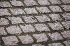 被修补的路面由红色和灰色鹅卵石制成 棋 免版税库存照片