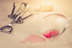 被倾倒的酒杯和拔塞螺旋在大理石背景之上/倾倒了红酒酒杯和拔塞螺旋在大理石背景之上 选择聚焦 免版税库存图片
