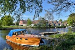 被停泊的小船和小木房子沿河 免版税库存图片