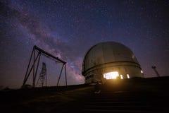被停泊的晚上端口船视图 一个特别天体物理学的观测所和一台起重机以满天星斗的天空为背景 免版税库存照片