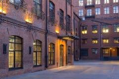 被停泊的晚上端口船视图 位于老工厂厂房的现代顶楼式办公室 砖安置红色 葡萄酒 与大Windows的大厦 图库摄影