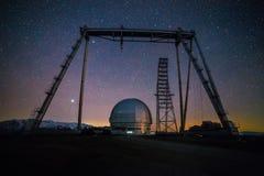 被停泊的晚上端口船视图 一个特别天体物理学的观测所和一台起重机以满天星斗的天空和白种人山为背景 免版税库存照片