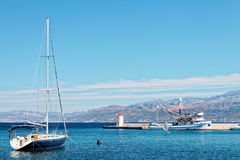 被停泊的yatch和渔拖网渔船在一个小镇Postira -克罗地亚,海岛Brac的港口 免版税库存图片
