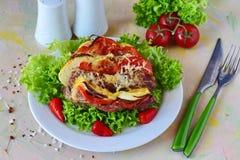 被充塞的猪肉在烤箱烤了用辣椒粉、蕃茄和乳酪在一块白色板材在抽象背景 库存图片