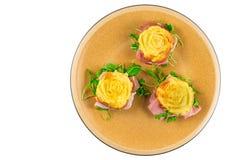 被充塞的菜肉馅煎蛋饼,烹调在微波炉,被塑造象一朵玫瑰,用火箭沙拉,斑点,烹调了火腿 免版税库存照片