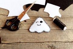 被充塞的鬼魂玩具,剪刀,毛毡板料,螺纹,在一张老木桌上的针 在家做的万圣夜白色鬼魂工艺 免版税库存图片