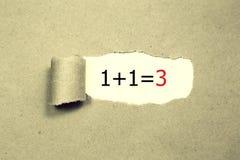 1+1=3被写在被撕毁的包装纸下 事务,技术,互联网概念 免版税库存图片
