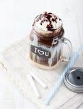 被冰的冷的咖啡、frapuccino与打好的奶油和巧克力糖浆在瓶子有黑板的我爱你在一张白色桌上 图库摄影