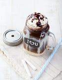 被冰的冷的咖啡、frapuccino与打好的奶油和巧克力糖浆在瓶子有黑板的我爱你在一张白色桌上 库存照片