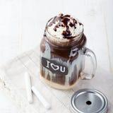 被冰的冷的咖啡、frapuccino与打好的奶油和巧克力糖浆在瓶子有黑板的我爱你在一张白色桌上 免版税库存图片