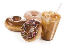 被冰的咖啡和三个油炸圈饼在白色背景 免版税库存图片