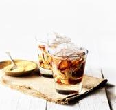 被冰的咖啡和奶油,餐巾,在白色背景的红糖 免版税库存图片