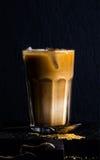 被冰的咖啡用在一块高玻璃的牛奶, moka罐,黑背景 免版税库存图片