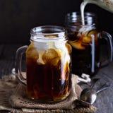 被冰的咖啡用在金属螺盖玻璃瓶的牛奶 免版税库存照片