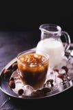 被冰的咖啡用牛奶和块菌状巧克力在玻璃 库存照片