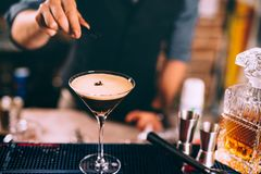 被冰的咖啡,威士忌酒根据爱尔兰鸡尾酒 准备饮料的侍酒者手 免版税库存图片