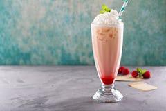被冰的奶昔用莓糖浆和打好的奶油 免版税库存照片