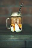 被冰的焦糖macciato咖啡用在瓶子,侧视图的牛奶 免版税库存图片