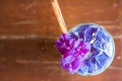 被冰的蝴蝶豌豆拿铁用在木桌上的牛奶 免版税库存图片