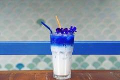 被冰的蝴蝶豌豆拿铁用牛奶和肉桂条在木桌上 库存图片