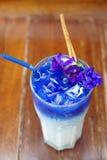 被冰的蝴蝶豌豆拿铁用牛奶和肉桂条在木桌上 免版税库存照片