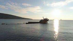 被击毁的船的天线沿反对发光的太阳的岩石海岸 射击 在海岸附近的老下沉的小船在大山 股票录像