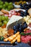 被分类的乳酪、新鲜水果和肉,垂直的选择聚焦 库存图片