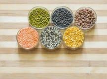 被分类的扁豆和豆类在玻璃碗,在一块砧板 图库摄影