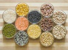 被分类的扁豆和豆类在玻璃碗,在一块砧板 免版税库存照片