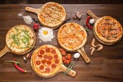 被分类的比萨用海鲜和乳酪,四乳酪,意大利辣味香肠,肉,在一个木立场的玛格丽塔酒用香料 库存照片