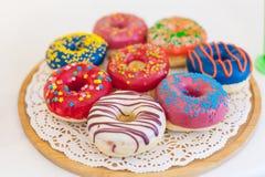被分类的油炸圈饼的图片在一个箱子的用结霜的巧克力,变粉红色给上釉并且洒油炸圈饼 免版税库存图片