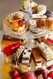 被分类的蛋糕、曲奇饼和果子在玻璃蛋糕站立 库存照片