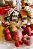 被分类的蛋糕、曲奇饼和果子在玻璃蛋糕站立 图库摄影