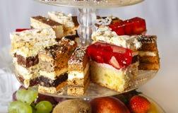 被分类的蛋糕、曲奇饼和果子在玻璃蛋糕站立 免版税图库摄影