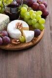 被分类的乳酪和新鲜的葡萄在委员会 库存照片