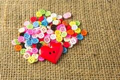 被分类的按钮和心脏按钮在浅褐色的大袋背景 免版税库存照片