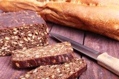 被分类的新鲜面包、在老木桌上隔绝的切片和刀子 图库摄影