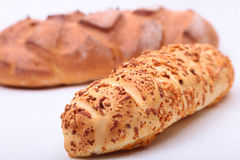 被分类的新鲜面包、在老木桌上隔绝的切片和刀子 免版税库存照片