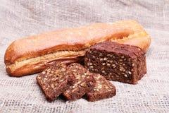 被分类的新鲜面包、在老木桌上隔绝的切片和刀子 库存照片