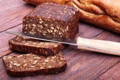 被分类的新鲜面包、在老木桌上隔绝的切片和刀子 免版税库存图片
